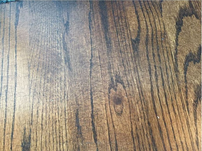 Sanding marks from a hand-held random orbital sander were obvious on this wood floor once stain was applied.